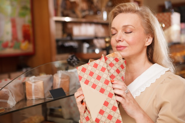 Beautiful mature woman smelling fresh bread loaf at the bakery