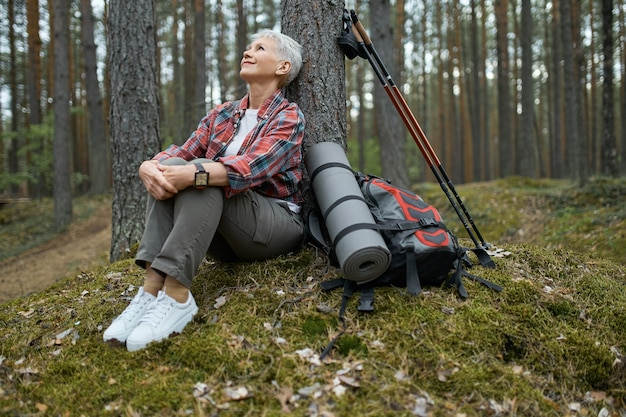 Beautiful mature woman in sneakers and activewear sitting on grass under pine having rest during nordic walking with sticks and backpack, looking up with relaxed carefree smile, breathing fresh air