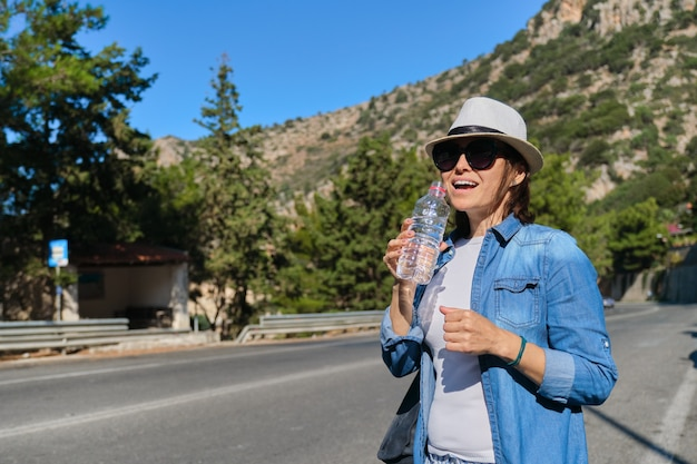 Beautiful mature woman standing on mountain road drinking water from bottle on hot sunny day. acting healthy lifestyle and healthy eating