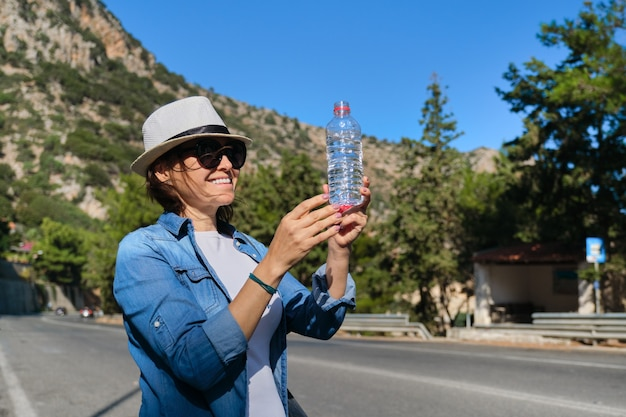 Beautiful mature woman standing on mountain road drinking water from bottle on hot sunny day
