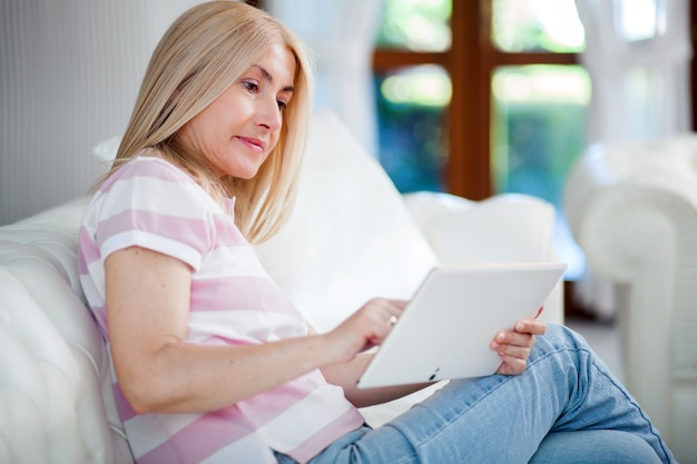 Beautiful mature woman using electronic tablet at home
