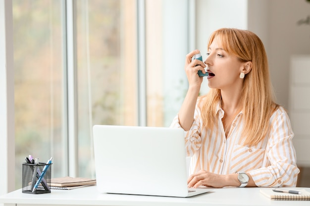 Красивая зрелая женщина с ингалятором астмы в офисе