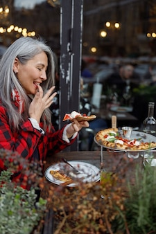 Beautiful matured asian woman is eating pizza in cafe terace
