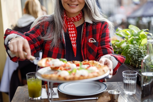 Beautiful matured asian woman is eating pizza in cafe terrace