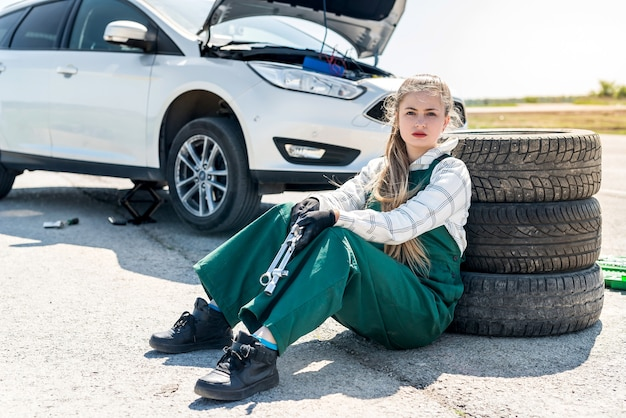 Beautiful mechanic with wrenches changing tires in car