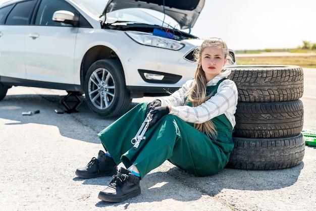 車の中でタイヤを交換するレンチを備えた美しい整備士