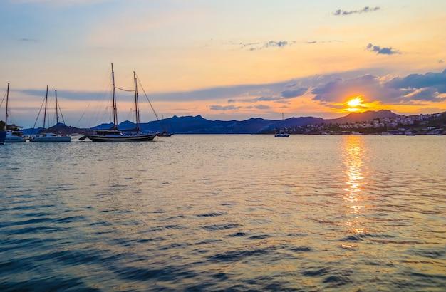 夕暮れ時の島々の山々とヨットのある美しい地中海沿岸