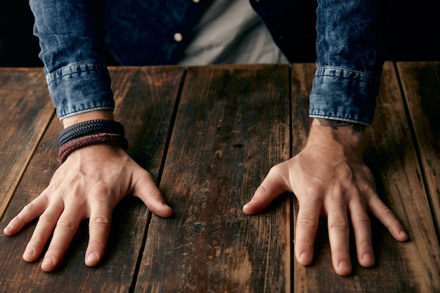 Beautiful men hands on table, jeans casual shirt, tattoo, wrist band, braceletes