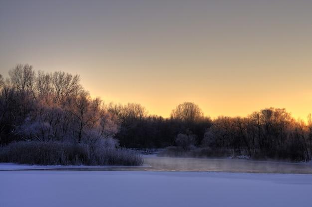 春の初めに川の美しい魅惑的な景色が溶け、涼しい春の夜に海岸沿いに木々が広がりました。コンセプトを解凍し、春先の日。コピースペース