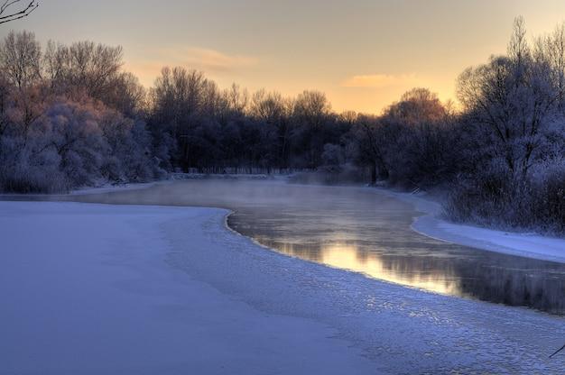 시원한 봄 저녁에 해안을 따라 나무와 함께 봄 초에 녹아 내린 강의 아름다운 매혹적인 전망