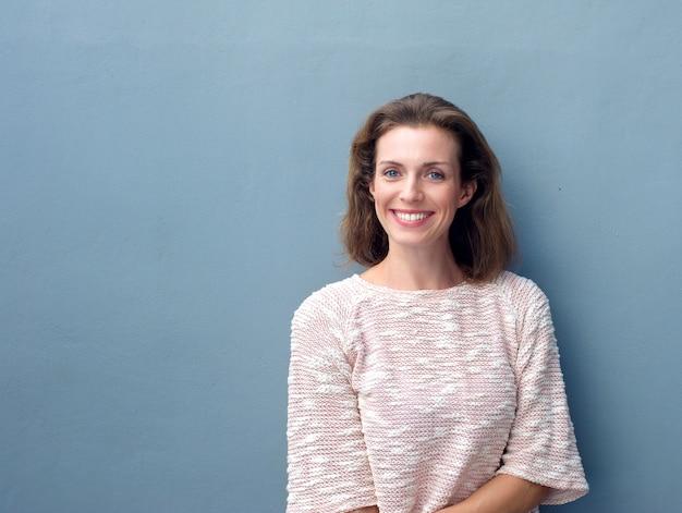 Красивая середине взрослая женщина улыбается на сером фоне