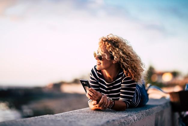 美しい中年の金髪の巻き毛の女性は、友人に電話する準備ができている現代の電話で夕日を眺めながら、屋外のレジャー活動で楽しんでリラックスしてください-きれいな女性の屋外の肖像画