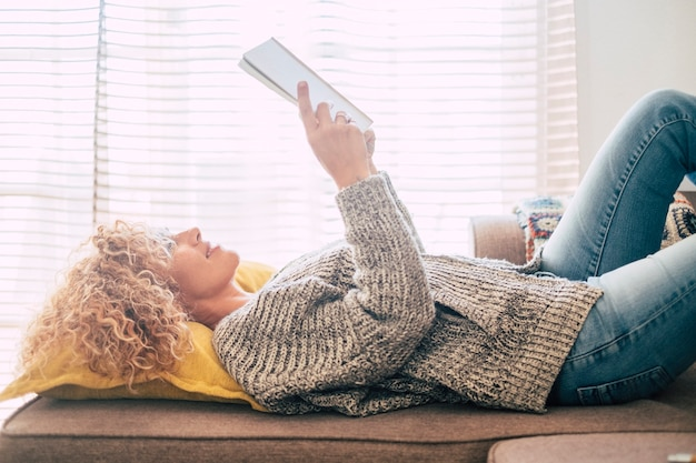Beautiful middle age female lay down on the sofa at home reading a book and enjoying the light from outside