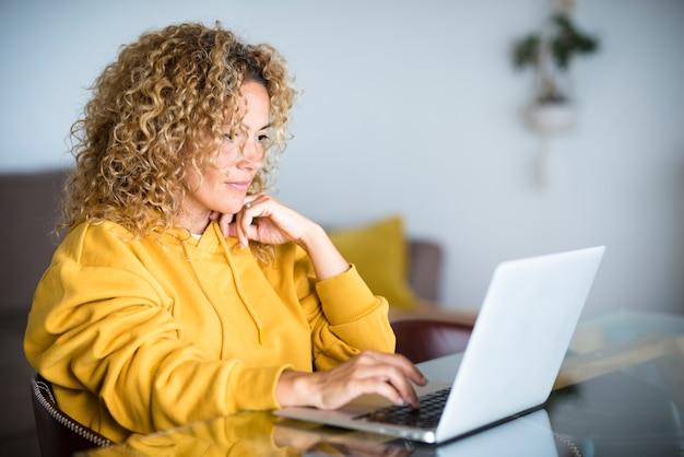 테이블에 앉아 집에서 컴퓨터 노트북에서 아름다운 중년 현대 여성 작업