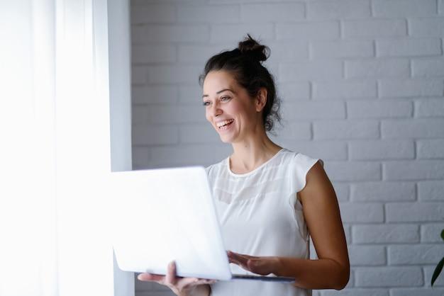그녀의 손에 태블릿을 들고 웃 고 아름 다운 중 년 여자.
