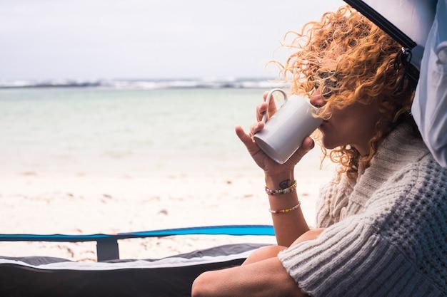 代替の休暇を楽しんでいる海岸の砂浜のテント内の無料キャンプで美しい中年の女性-白人の現代のライフスタイルの人々のための旅行と冒険の旅のコンセプト