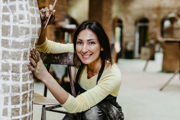 ゴージャスな彫刻に取り組んでいる美しい中年女性のプロの彫刻家。
