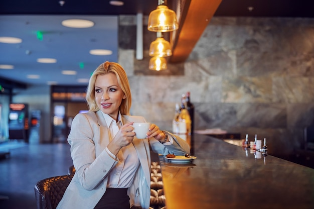 A beautiful middle-aged businesswoman sitting in a hotel cafe and enjoying her coffee. she waiting for a business meeting. free time, enjoyment, respite, lifestyle