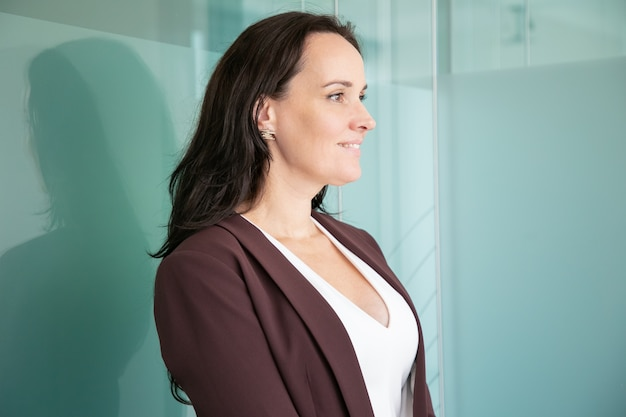 Beautiful middle-aged businesswoman standing and looking away