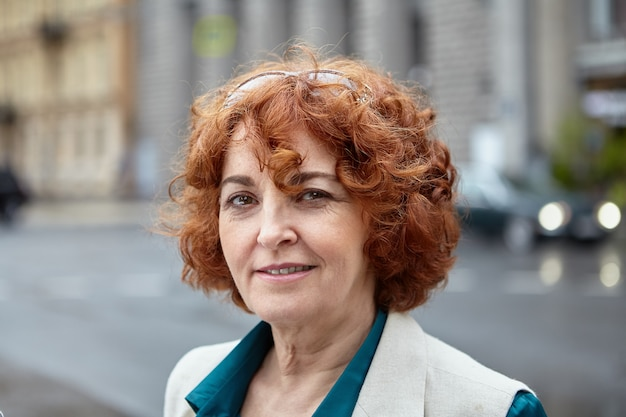 Beautiful middle-aged  businesswoman with short curly red hair is posing on city street.