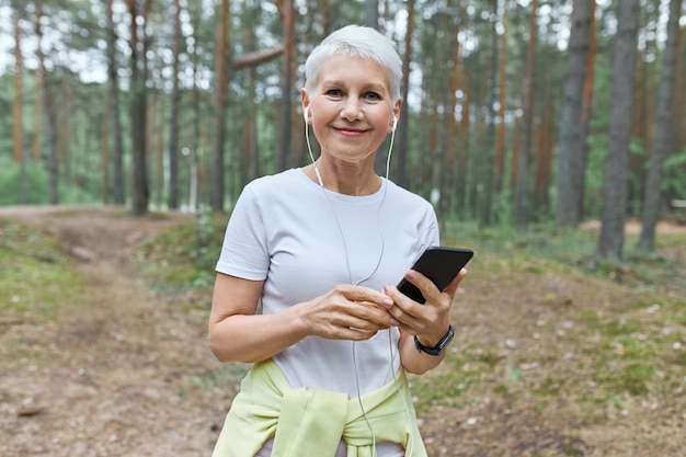 Beautiful middle aged caucasian woman with short hair enjoying summer morning outdoors, going to have cardio workout, choosing music tracks on mobile phone