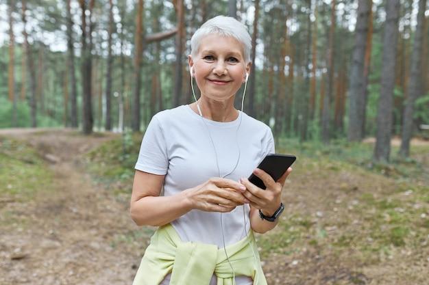 夏の朝を屋外で楽しんだり、有酸素運動をしたり、携帯電話で音楽トラックを選んだりする短い髪の美しい中年白人女性