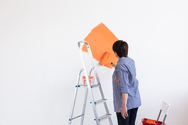 페인트 롤러로 벽을 그리는 아름다운 중년 여성. 아름 다운 영의 초상화