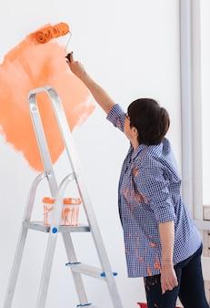 Красивая женщина средних лет красит стену валиком.