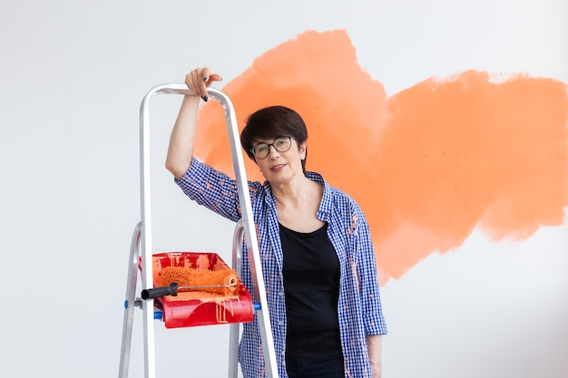 Beautiful middle-aged female painting the wall with paint roller.