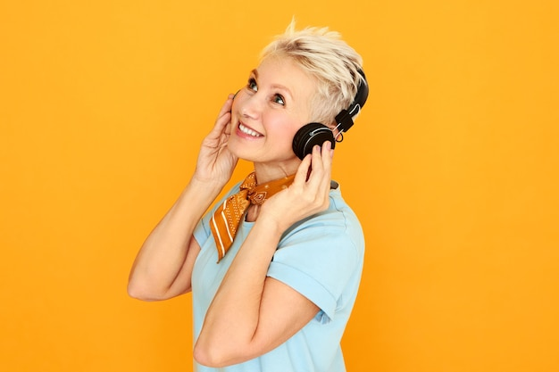 Beautiful middle aged female wtih blue eyes and short hair posing against yellow background looking up with cheerful joyful smile, listening to music using wireless headphones.