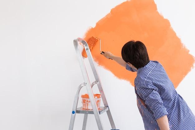ペイントローラーで壁を塗る美しい中年の女性。若い美しいの肖像画