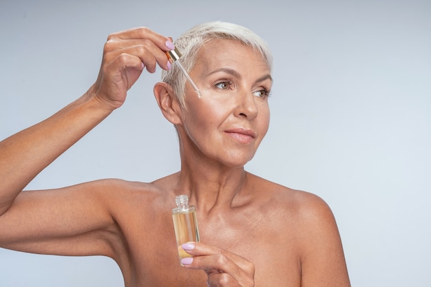 Beautiful middle aged lady looking into camera and putting serum on her cheek