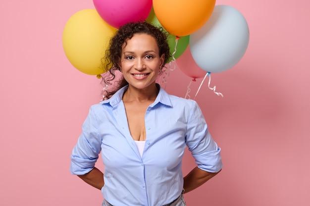 彼女の背中の後ろにマルチカラーのエアボールを持って、カメラを見て歯を見せる笑顔で笑っている青いシャツを着た美しい中年の混血見事な女性。コピースペースとピンク色の背景
