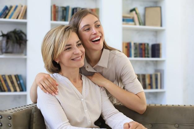 Красивая мама среднего возраста и ее взрослая дочь обнимаются и улыбаются, сидя на диване у себя дома.