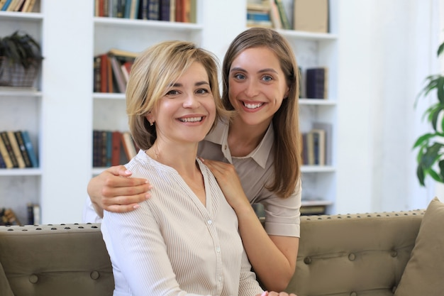 Beautiful middle aged mom and her adult daughter are hugging, looking at camera and smiling.