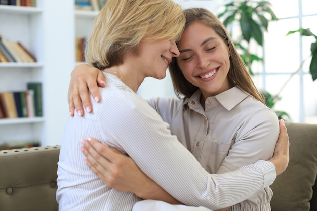 Beautiful middle aged mom and her adult daughter are hugging and smiling while sitting on couch at home.