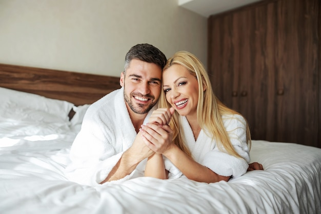 Beautiful middle-aged smiling couple with a fresh face lie on a bed in a hotel room in a white bathrobe