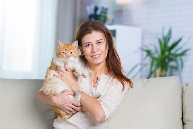 Красивая женщина средних лет дома на диване в интерьере