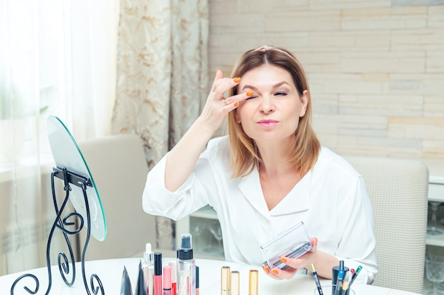 Beautiful middle aged woman blogger shows how to use cosmetics. live video blog recording at home. the modern version of the work at home.
