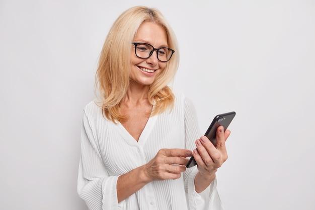 Bella donna di mezza età chat sul telefono cellulare felice di ricevere un messaggio dalla figlia sorride felicemente indossa camicetta bianca ordinata e occhiali da vista