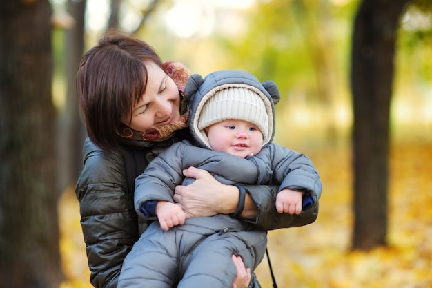 Beautiful middle aged woman and her adorable little grandson in the autumn park