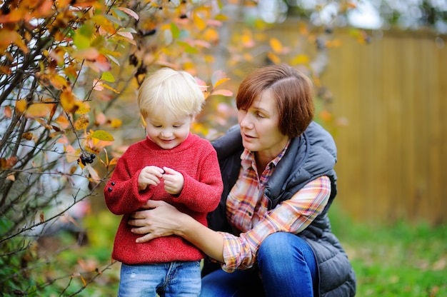Beautiful middle aged woman and her adorable little grandson enjoying black currants in domestic garden