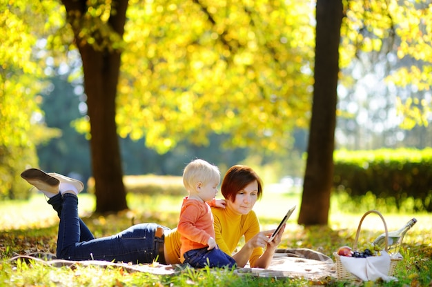 Beautiful middle aged woman and her adorable little grandson having a picnic in sunny park. family using tablet pc together