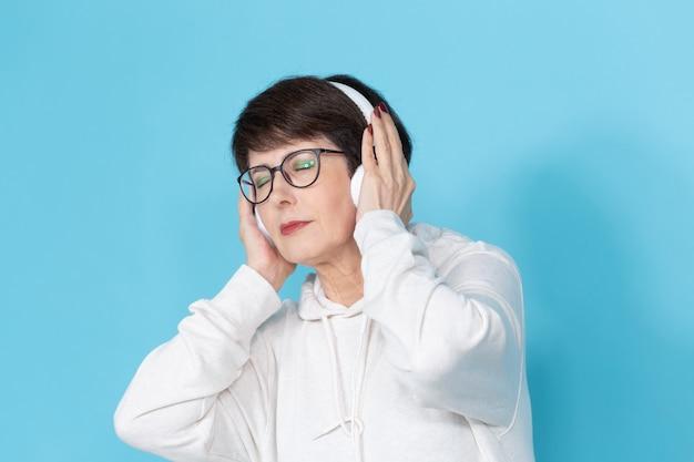 白いセーターと眼鏡をかけた美しい中年女性が赤青の壁にポーズをとって音楽を聴いています。好きな趣味のコンセプト。 。