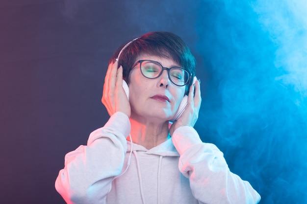 흰색 스웨터와 안경에 아름다운 중년 여성이 포즈를 취하는 동안 음악을 듣고있다