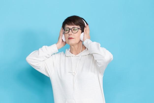 白いセーターとメガネの美しい中年女性がポーズをとっている間音楽を聴いています