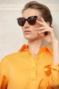 サングラスと明るい服を着た美しい中年女性、クローズアップ。
