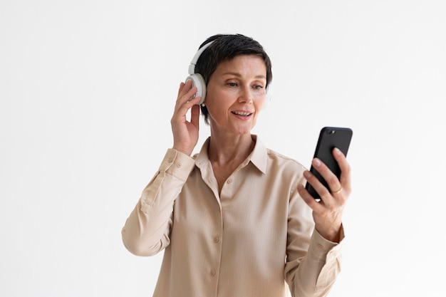 Beautiful middle aged woman listening to music through headphones