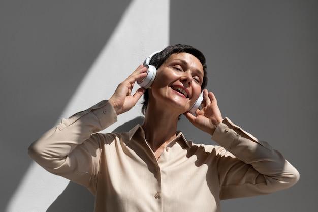 헤드폰을 통해 음악을 듣는 아름다운 중년 여성