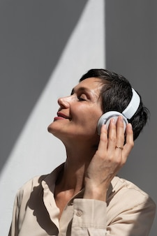 Красивая женщина средних лет, слушающая музыку через наушники
